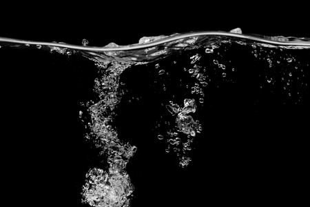 Clear water surface on a black with ripple and bubbles Stockfoto