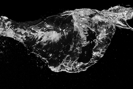 Clear water splash on a black with ripple and bubbles Stock Photo