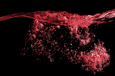 Clear splash surface of red wine or juice water with drops. Isolated on a black