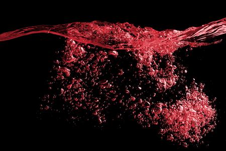 레드 와인 또는 쥬 스 물 방울과의 명확한 스플래시 표면. 블랙에 절연