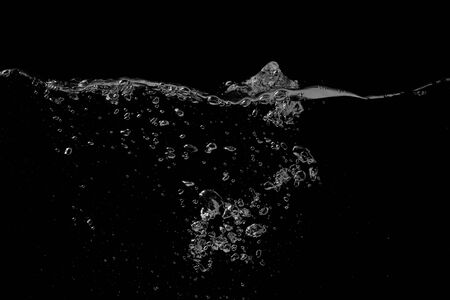 Clear water liquid splash wave surface with ripple and bubbles on a black nature background