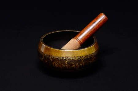 Tibetan singing bowl on dark background photo