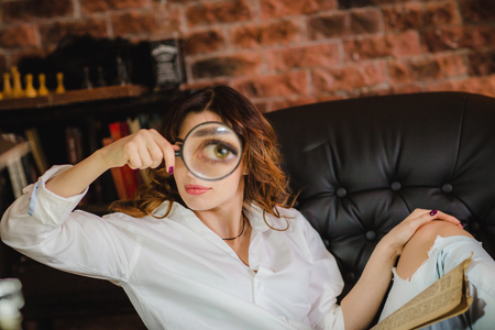 Big teeth of pretty brunette woman puts in magnifying glass