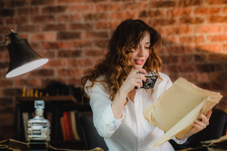 young brunette woman in white shirt quickly doing photo in office the contents of papers and maps on table