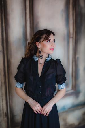 Pretty brunette model posing near art wall