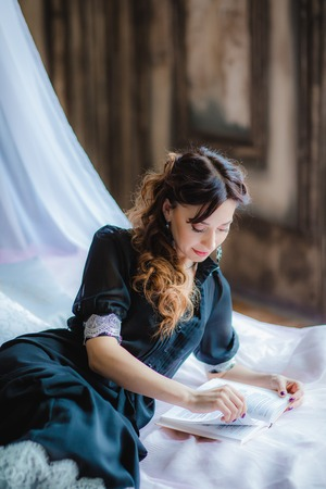 Portrait of pretty brunette model lies on bed with canopy and reading a book