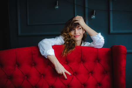 pretty young brunette model in white short posing behind red sofa and smiling
