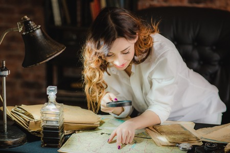 funny woman looking through a magnifying glass to a documents on table Foto de archivo