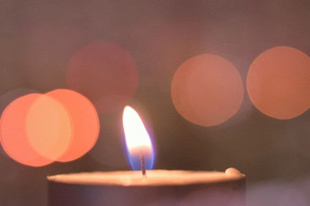Holiday background of burning candle with blurred lights during Indian festival of Diwali
