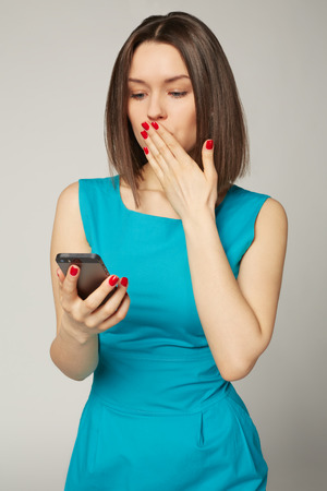 Businesswoman with smartphone receiving shocking news. Grey background