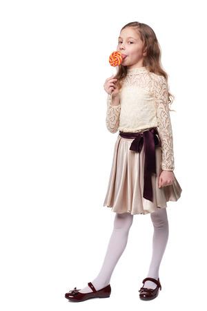 paletas de caramelo: Una ni�a tiene una gran espiral Lollypop aisladas en blanco Foto de archivo