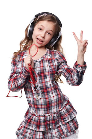 Pretty little girl singing in imaginary microphone with headphones on his head isolated over white photo