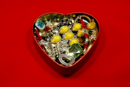 heart shaped box filled with jewelry on red background photo