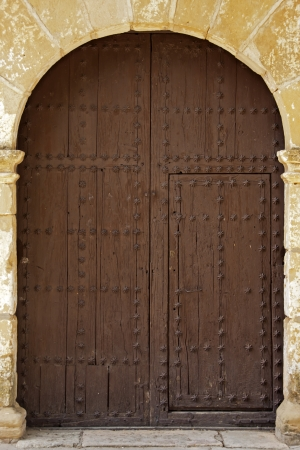 Closed Oval Wooden Doors With Iron Fittings On The Stone Wall photo