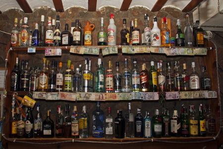 バーの後ろに多くのアルコール飲料が付いている棚
