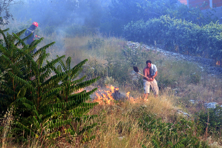 Zrnovnica, Split, Croatia - July 17, 2017: Man fighting with the massive wildfire burning down the forest and villages around city Split Editorial