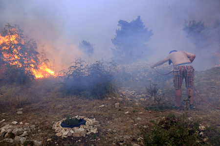 Zrnovnica, Split, Croatia - July 17, 2017: Man fighting with the massive wildfire burning down the forest and villages around city Split Stock Photo