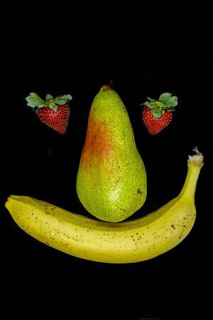 Smiling fruit face with strawberry eyes isolated on black background