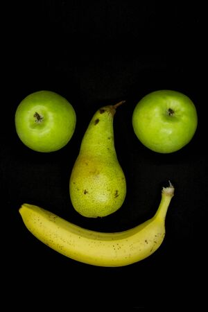 Smiling fruit face with apple eyes isolated on black background 스톡 콘텐츠