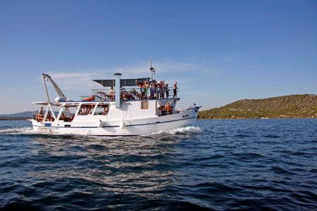 Betina, Croatia - 15 August, 2011: Tourist motor boat Rom full of tourists during the regatta Latin Sail Editorial