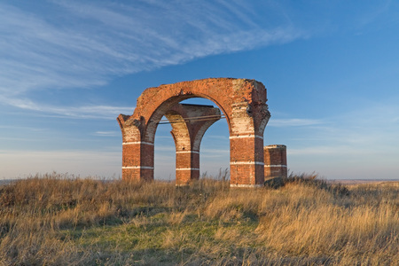 Brick arches of old church ruins solitary in the field.