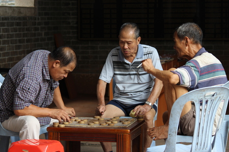 old folks play chess during leisure time