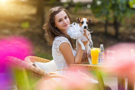 cute love: Young, beautiful girl has received a long-awaited gift - dog breed Jack Russell Terrier. Girl sitting at a restaurant or cafe table outdoors. Wonderful summer, sunny day.