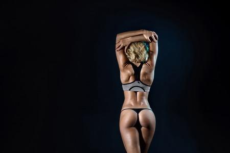 mujeres de espalda: Mujer joven del ajuste hermoso con la carrocería muscular delgada en ropa deportiva posando en el estudio. longitud completa, vista lateral, tiro del estudio, fondo negro.