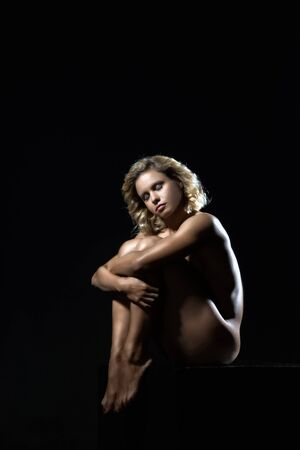 rigid: Young, strong athlete posing on a dark background under the rigid studio lighting sources