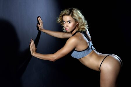 briefs: Sport, slim young girl with muscular body posing in the studio on a dark background. Girl dressed in athletic briefs and sports top. Looking into the camera Stock Photo
