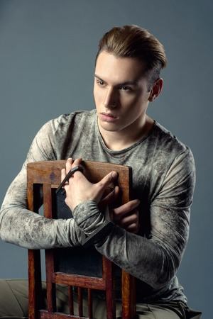 black fashion model: Young, elegant, sexy, fashion, handsome, caucasian, man sitting in the  chair. Stylish portrait of a man in casual clothing in the studio which looks directly into the frame.