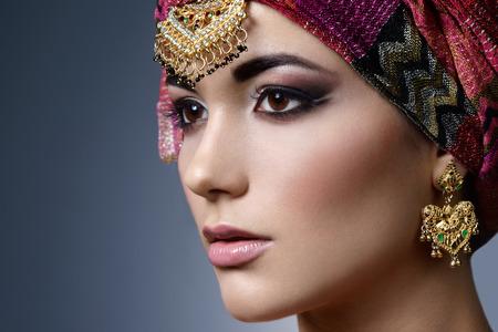 Beautiful fashion femme est portrait avec des accessoires orientaux. Indian fille arabe avec couleur turban et de beauté bijoux. modèle hindou avec un maquillage parfait. Inde. Asie
