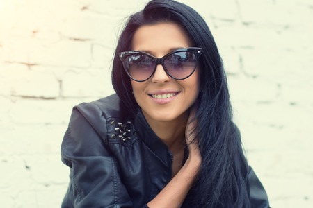 looking directly at camera: Beautiful brunette girl standing at white brick wall. She dreams, smiling, thinking about beauty. She is dressed in blue jeans and a black leather jacket. Looking directly into the camera