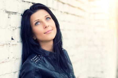 Schönes Brunettemädchen, das an der weißen Backsteinmauer steht. Sie träumt, lächelt, denkt über Schönheit nach. Sie trägt blaue Jeans und eine schwarze Lederjacke. Sieh nach oben