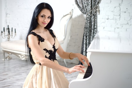 Charming brunette with long hair in evening dress playing the piano