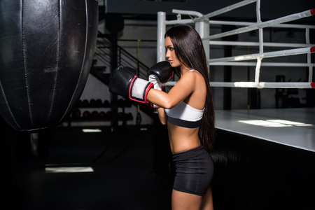Portrait of a woman boxer, aggressive and ready to fight. Punching Bag Punch.