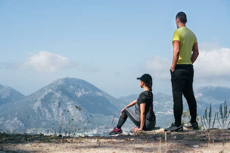 The couple stand a hill and looks at the unleashed landscape. Seascape with a birds-eye view.