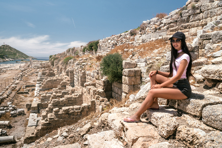 The girl is on vacation. A woman at the excursion in the ancient city. Active tourism. Beautiful girl sits on a stone and looks at the ruins of the ancient city of Knidos Stock Photo