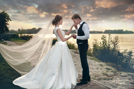 The bride and groom in wedding dresses on natural background.The stunning young couple is incredibly happy. Wedding day. Newlyweds are walking along the river bank at sunset. Happy and loving people