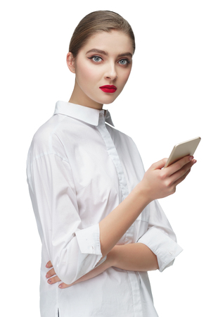 Young woman isolated on gray background looking at smartphone, smiling openly while holding smartphone in both hands.