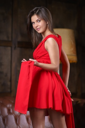 An unbelievable sensual and beautiful young girl in a red dress. A woman is posing and undressing in front of the camera. Erotic photos