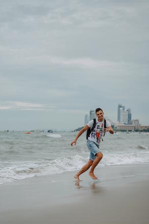 바다 해안에서 휴가를 즐기는 젊은 남자. 달리고, 점프하고, 해변에서 즐거운 시간을 보내세요. 바다에서 재미. 저녁 파타야, 태국.