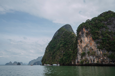 Vacation in sunny Asia. Excursion between the islands of Pang Nga Bay. Activities and adventures. Fancy rocks in the water.