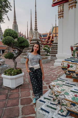 Fabulous, mystical, Buddhist Asian temple. Woman impressed with the beauty of the place. Tourist girl walks through the temple between the ancient pagodas Wat Pho in Bangkok - Temple of Reclining Buddha.