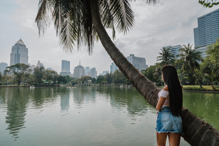 View of the modern metropolis. Bangkok, Thailand. Tourist girl enjoying city park view.