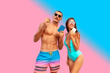 A girl and a guy in beachwear getting ready for summer vacation. Quarantine is over. Credit cards, passports and telephone are the main tourist assistants.