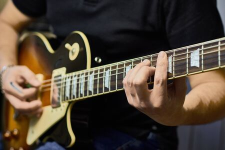 man plays electric guitar, close-up, lifestyle, making music