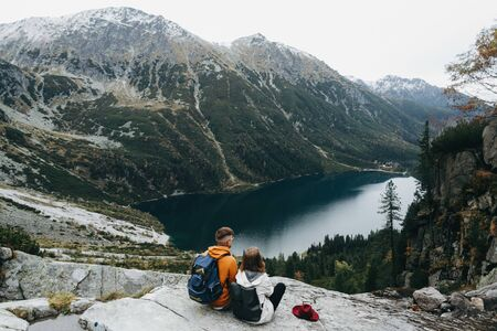 Lovely couple travelling together in the mountains, walking around the lake Morskie oko in Tatry. Amazing girl in a white jacket. Stunning view.