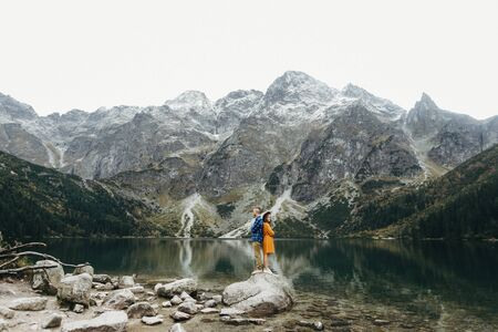 Lovely couple travelling together in the mountains, walking around the lake Morskie oko in Tatry. Amazing girl in yellow dress. Stunning view.