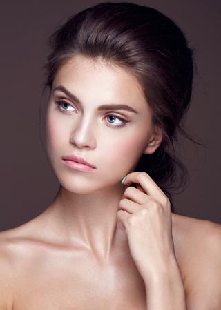 femme romantique: Glamour portrait de la belle femme modèle avec le maquillage frais du jour et romantique ondulée coiffure. Mode surligneur brillant sur la peau, les lèvres brillantes sexy maquillage et sourcils sombres